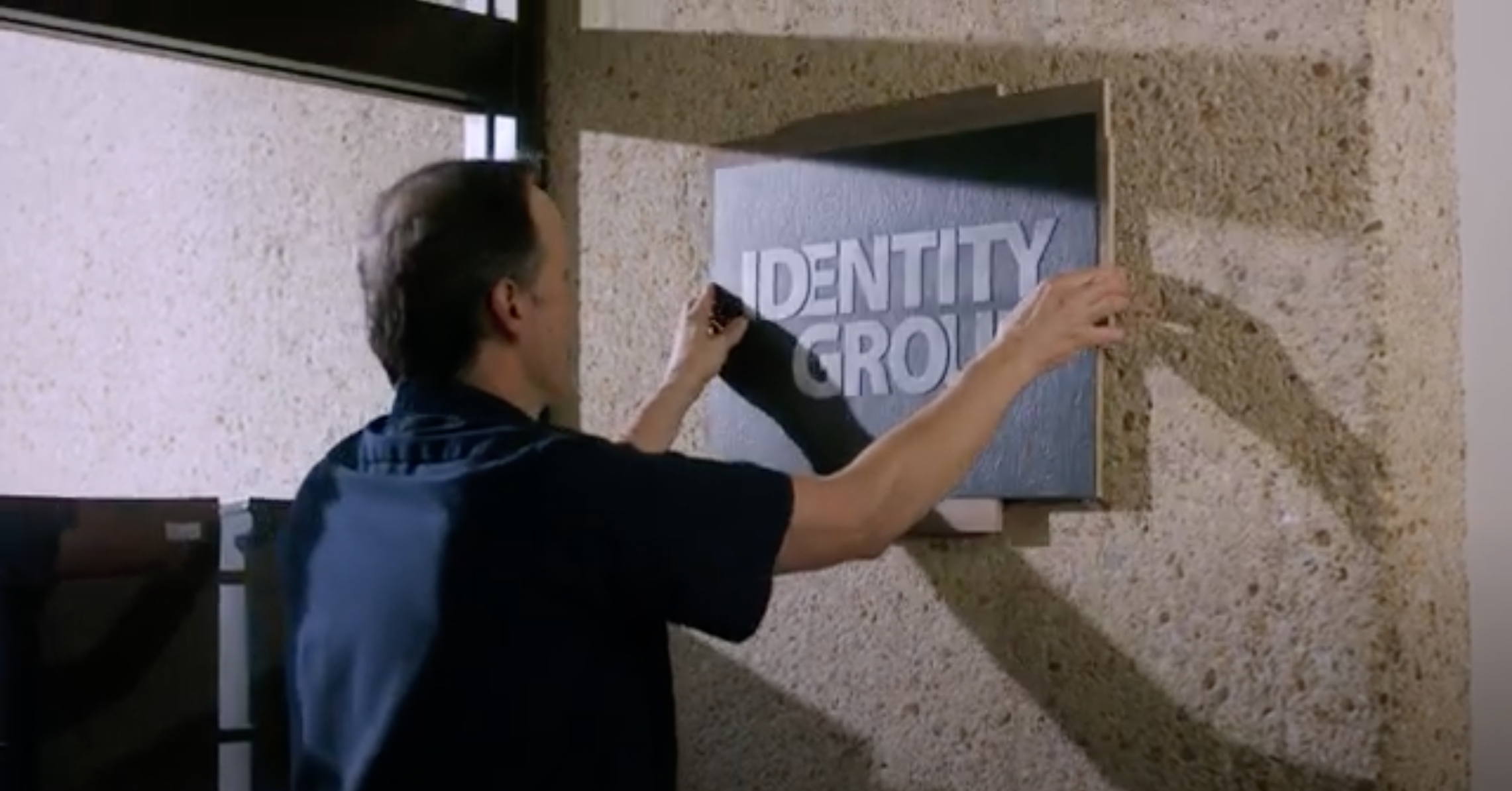 Man hanging Identity Group Sign on concrete wall